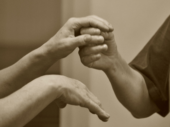 Photo of touching hands, copyright Roseaux Dansants